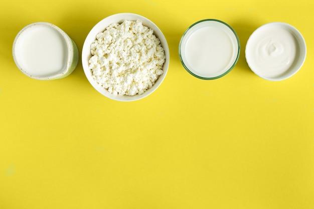 Produtos lácteos, leite, creme azedo, queijo cottage, plano, sobre fundo de papel amarelo com espaço de cópia