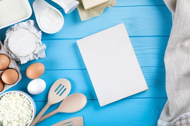 Produtos lácteos na mesa de madeira azul. creme de leite, leite, queijo, ovo e manteiga.