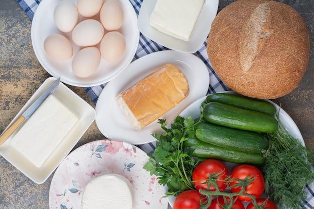 Produtos lácteos, pão e vegetais no café da manhã.