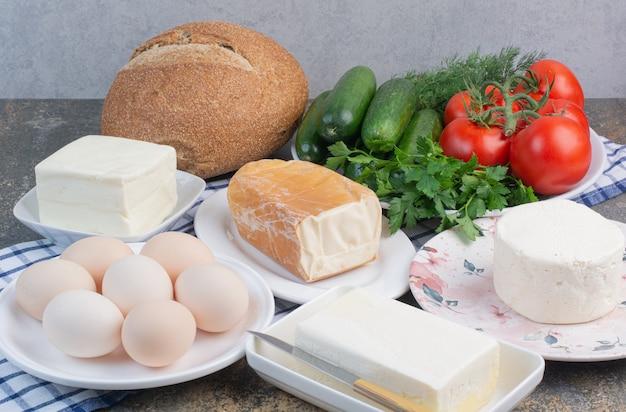 Produtos lácteos, pão e vegetais no café da manhã