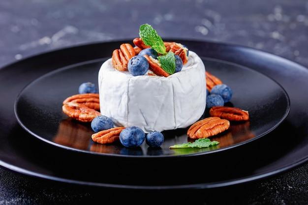 Produtos lácteos: queijo brie branco amadurecido com mirtilo, nozes com hortelã por cima em uma placa preta sobre uma mesa de concreto escura, close-up