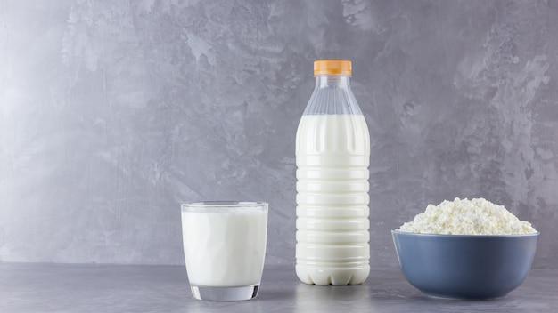 Produtos lácteos saudáveis em um fundo cinza. leite e queijo cottage