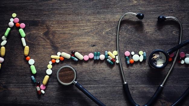 Produtos médicos para o tratamento de doenças cardíacas. o conceito de dependência da saúde do coração em comprimidos. comprimidos e estetoscópio sobre fundo de madeira.
