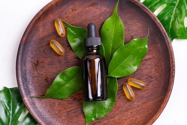 Produtos naturais de beleza com cápsulas de gel omega 3 e soro em garrafas de vidro, folhas verdes na placa de madeira em branco