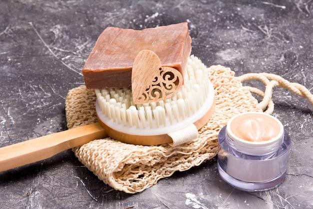 Produtos naturais de cuidado corporal e escova de massagem, em um fundo escuro, estilo de vida ecológico