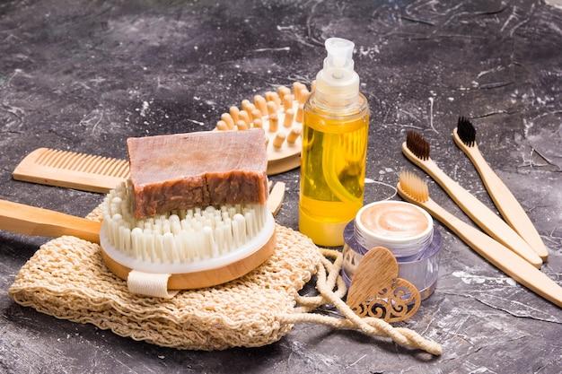Produtos naturais para o corpo em casa, escova de massagem anticelulite de madeira, toalha de malha, escovas de bambu, óleo, sabonete doméstico e esfoliante corporal em superfície escura