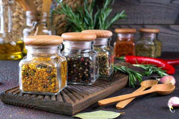 Produtos para cozinhar na cozinha, utensílios de cozinha, ervas, especiarias secas coloridas em frascos de vidro na superfície escura