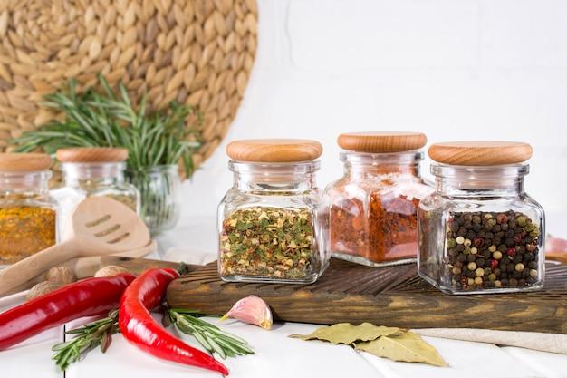 Produtos para cozinhar na cozinha, utensílios de cozinha, ervas, especiarias secas coloridas em potes de vidro na parede branca