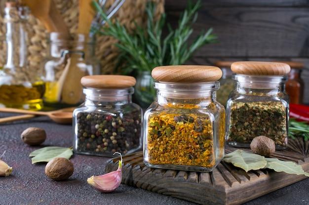 Produtos para cozinhar na cozinha, utensílios de cozinha, ervas, especiarias secas coloridas em potes de vidro