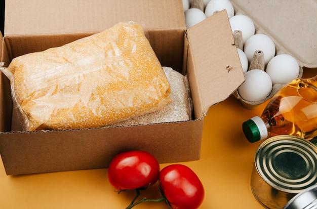 Produtos para doação em amarelo. legumes, cereais e alimentos enlatados.