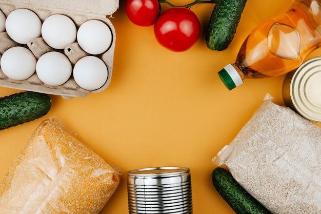 Produtos para doação em um fundo amarelo. legumes, cereais e alimentos enlatados. doações de alimentos copiam o espaço.