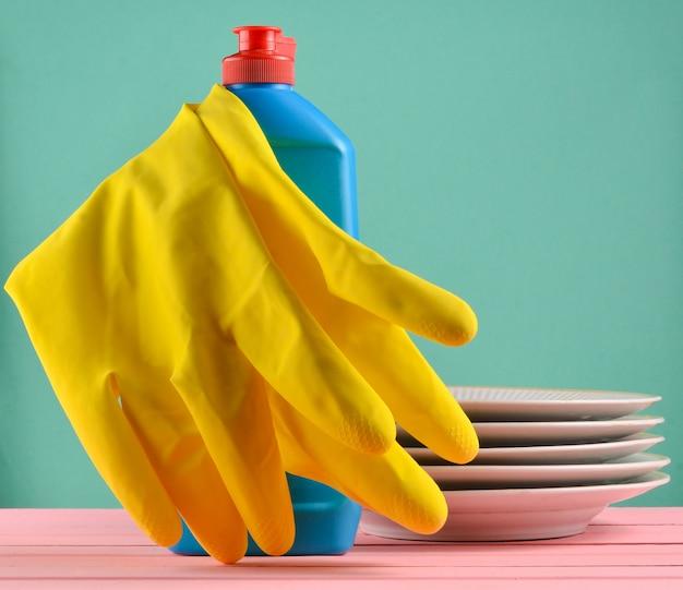 Produtos para lavar a louça em uma mesa isolada. copie o espaço
