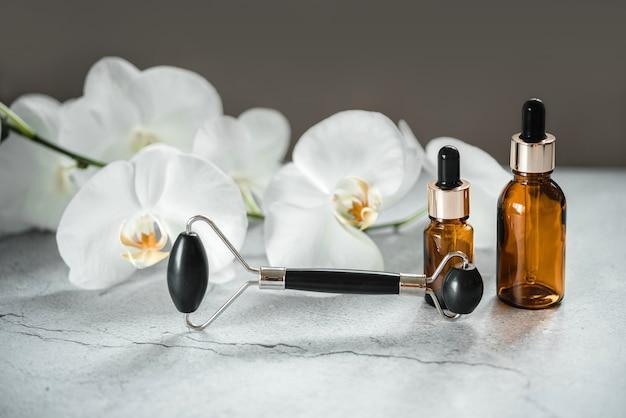 Produtos para o corpo e a pele, frascos conta-gotas e rolo de massagem guasha de pedra obsidiana no banheiro com flores de orquídea, maquete de marca de produto cosmético de spa
