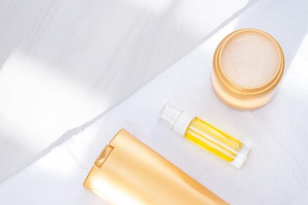 Produtos para o corpo e cabelos, artigos de toalete com toalha, luz solar. cuidados e conceito limpo para a pele, cabelos e corpo. postura plana, cópia espaço.