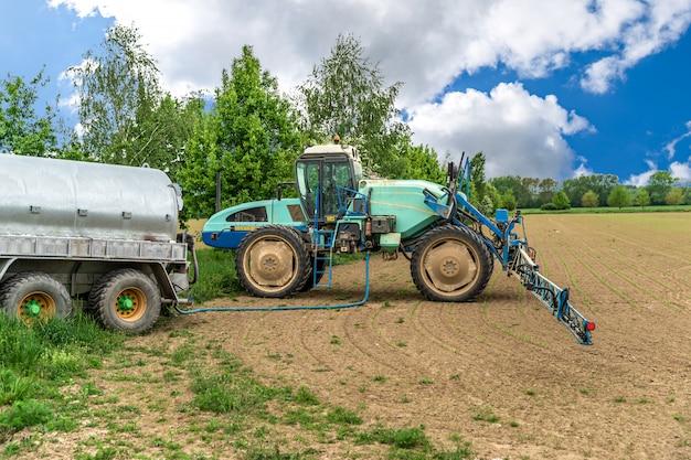 Produtos químicos contra ervas daninhas reabastecidos no tanque de um trator com um pulverizador