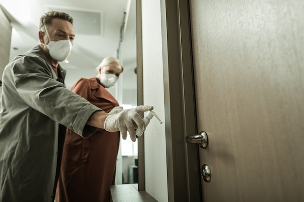 Produtos químicos do recipiente. homem com respiradores profissionais cobrindo a mão da porta com spray enquanto seu confederado fica para trás