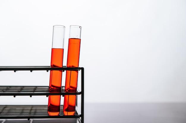 Produtos químicos laranja em um tubo de vidro de ciência dispostos em uma prateleira