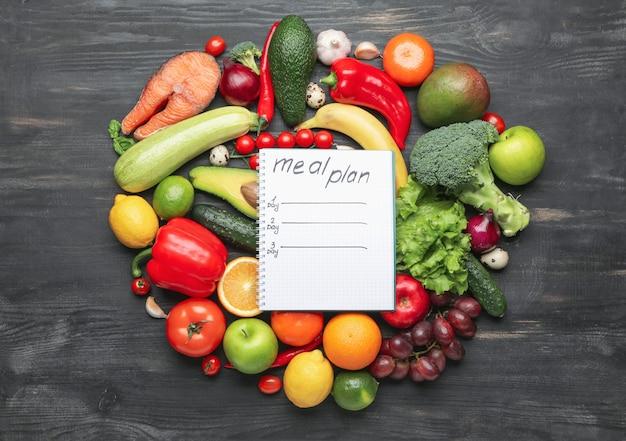 Produtos saudáveis e plano de refeições em superfície escura