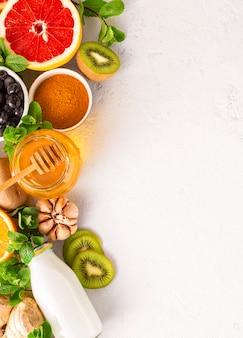 Produtos saudáveis para imunidade, aumentando em fundo branco, com vista superior do espaço cópia. legumes e frutas para impulsionar o sistema imunológico