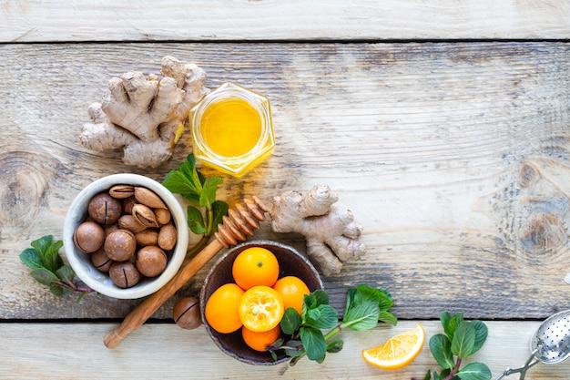 Produtos saudáveis para imunidade, aumentando em fundo de madeira com vista superior do espaço cópia. limão, nozes, gengibre para o sistema imunológico