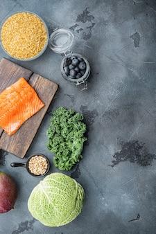 Produtos saudáveis, planos leigos, na mesa cinza.