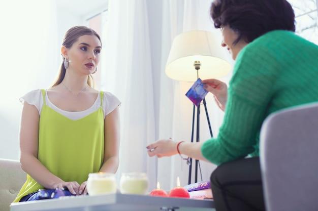 Profecia sobre o futuro. mulher bonita séria ouvindo a cartomante enquanto quer saber o futuro