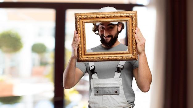 Profesional pintor segurando uma moldura barroca