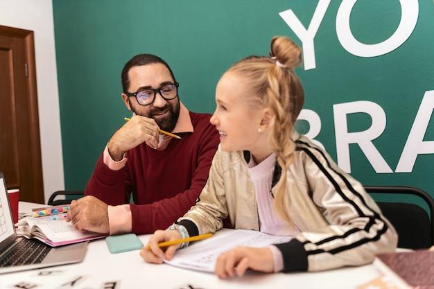 Professor adulto barbudo de cabelo escuro divertido usando óculos e seu aluno parecendo divertido enquanto trabalhava na aula
