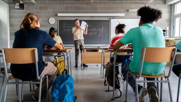 Professor adulto faz perguntas a alunos multirraciais. aluno levanta a mão faixa horizontal