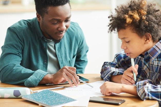 Professor africano sentado à mesa junto com o aluno e explicando-lhe o novo material