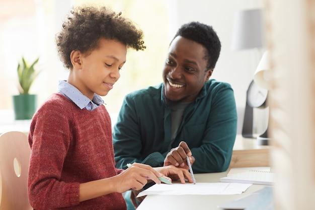Professor africano sorridente ensinando seu aluno apontando para um papel e explicando o novo material na mesa de casa
