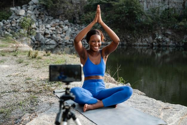 Professor afro-americano de ioga praticando ao ar livre