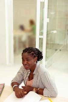 Professor afro-americano. linda pessoa do sexo feminino apoiando os cotovelos na mesa enquanto fala com a aluna