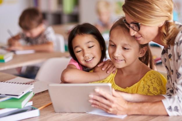 Professor ajudando alunos com tablet digital