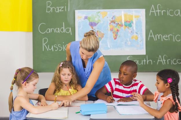 Professor, ajudando as crianças com os trabalhos de casa na sala de aula