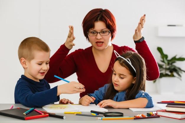 Professor ajudando crianças com lição de casa em sala de aula na escola