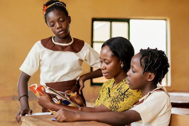 Professor ajudando crianças na aula