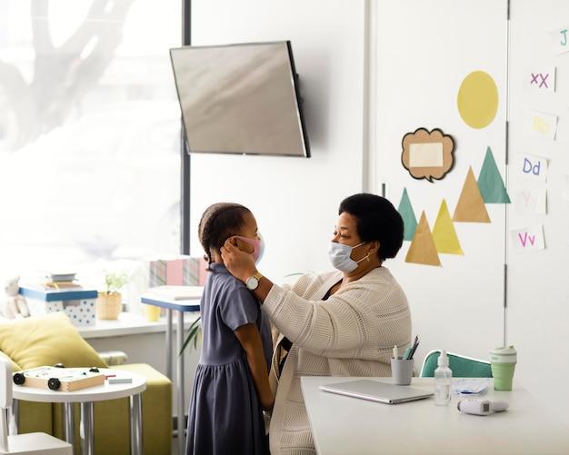 Professor ajudando um aluno a colocar uma máscara médica