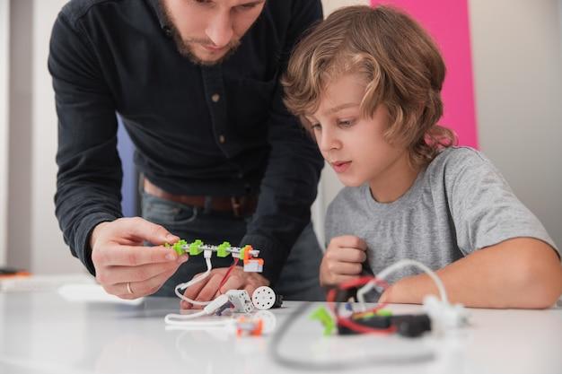 Professor ajudando um aluno atento a criar um robô durante a aula de tecnologia na escola