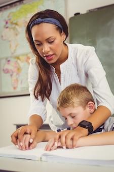 Professor ajudando um garoto com sua lição de casa na sala de aula