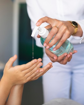 Professor ajudando uma criança a desinfetar as mãos