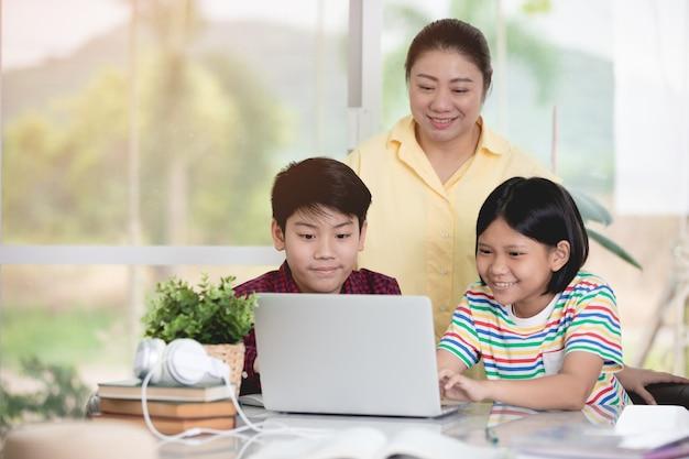 Professor asiático e miúdos que divertem usando o computador portátil.