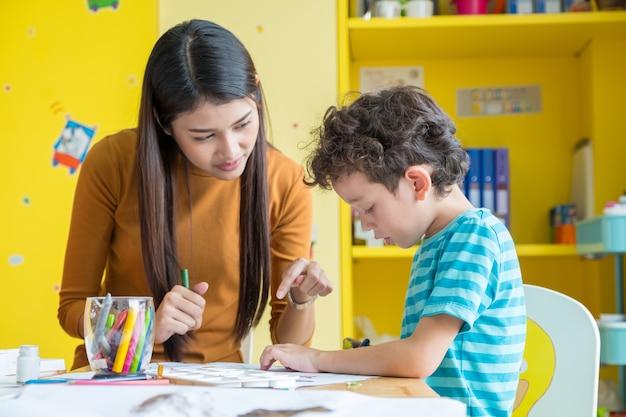 Professor asiático professor ensinando garoto menino a pintar livro colorido na mesa na sala de aula