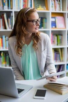 Professor atencioso usando tablet digital com laptop e telefone na mesa na biblioteca