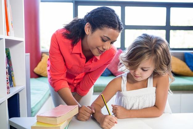 Professor, auxiliando a garota escrevendo no caderno na biblioteca