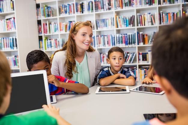Professor bonito jovem tendo aula para crianças com seu tablet