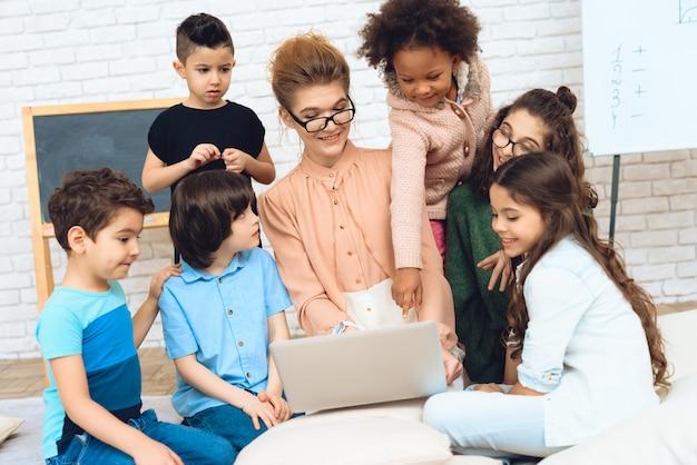 Professor bonito senta-se com as crianças da escola está olhando para laptop