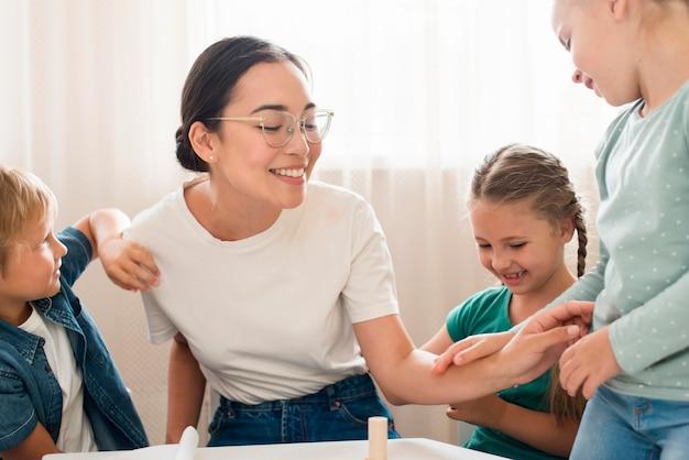 Professor brincando com crianças dentro de casa