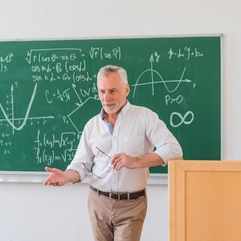 Professor cessante de pé no pódio e explicando o material