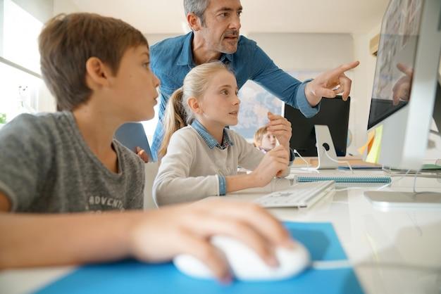 Professor com alunos em uma aula de informática